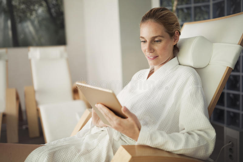 Picture of beautiful woman relaxing in spa center. Picture of beautiful woman relaxing and using tablet in spa center royalty free stock photos