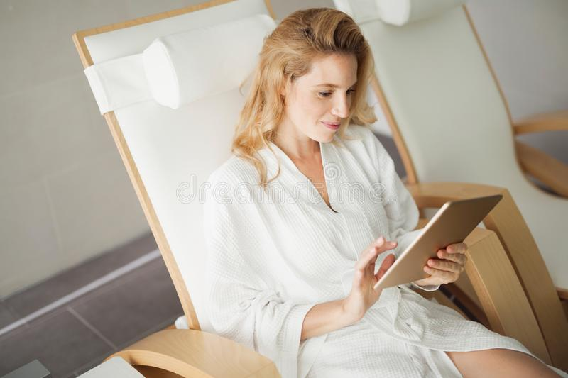 Picture of beautiful woman relaxing in spa center. Picture of beautiful woman relaxing and using tablet in spa center royalty free stock images