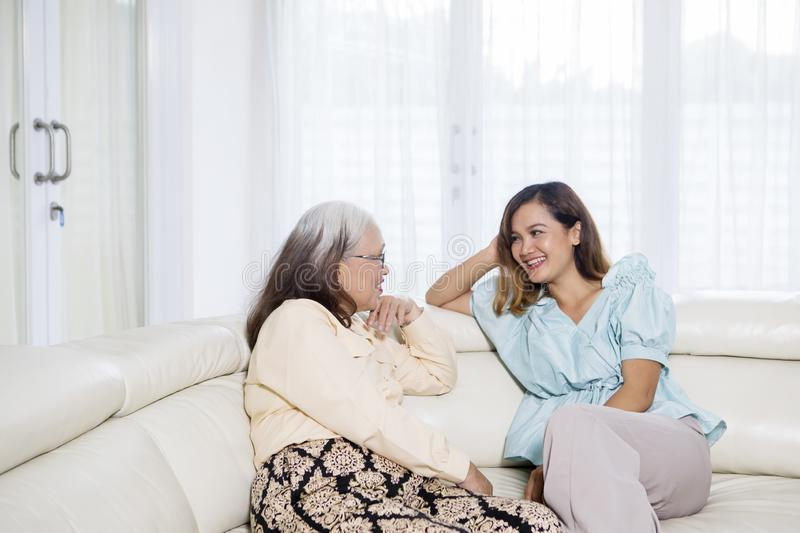 Beautiful woman chats with her mother at home. Picture of beautiful women chatting with her mother while sitting together on the couch. Shot at home royalty free stock photography