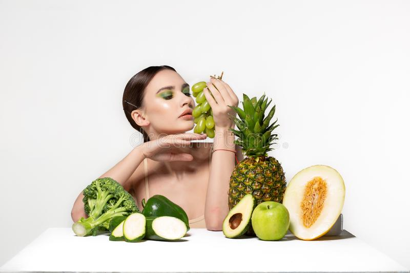 Picture of beautiful young brunette woman with fruits and vegetables on the table, holding green grapes in hand isolated stock image