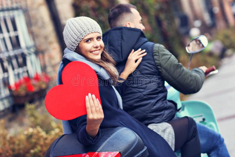 Beautiful young couple holding hearts while riding scooter in city in autumn royalty free stock image