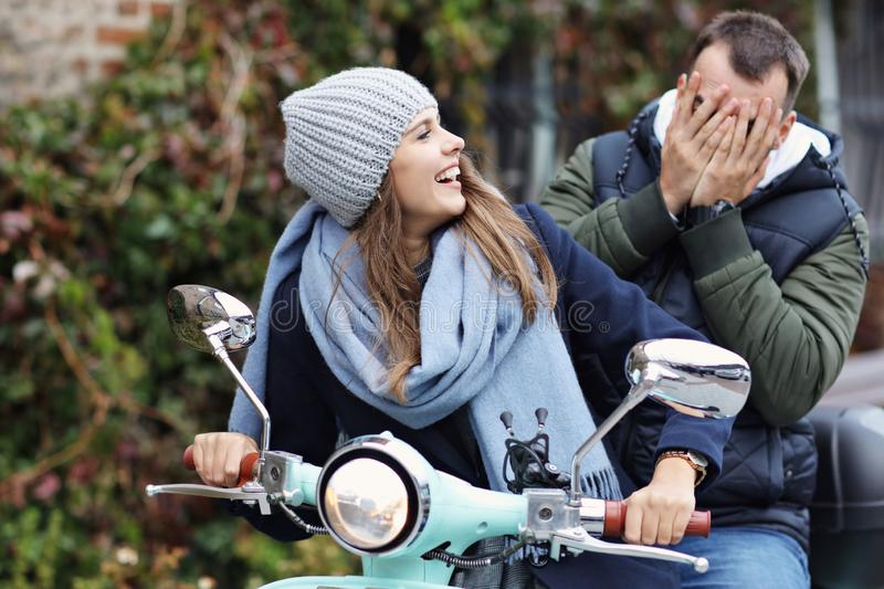 Beautiful young couple smiling while riding scooter in city in autumn stock image