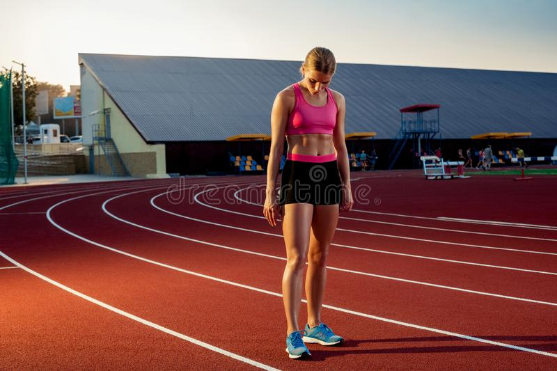 Picture of beautiful young European female runner or sprinter standing on outdoor stadium track, feeling exhausted after royalty free stock photography