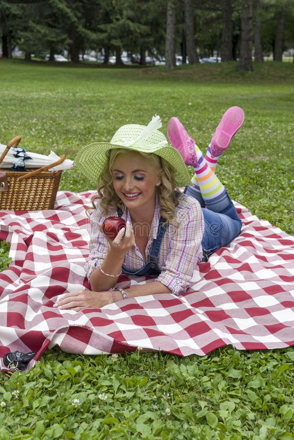 Attractive young blond woman posing outdoors during picnic royalty free stock photo