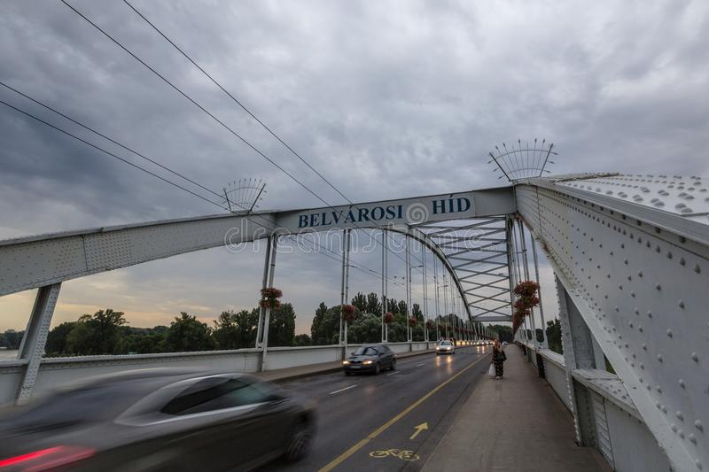 Belvarosi Hid bridge, with cars and pedestrians passing by, on the tisza river. The bridge connects the two parts of this city stock photo