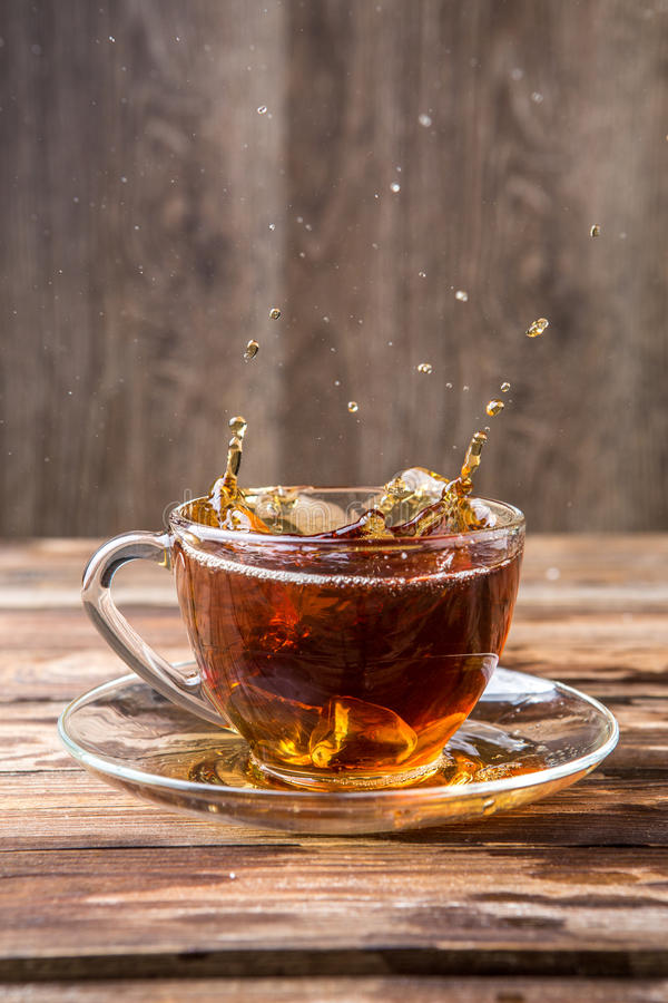 Picture of black tea spill. In glass mug on wooden table royalty free stock photos