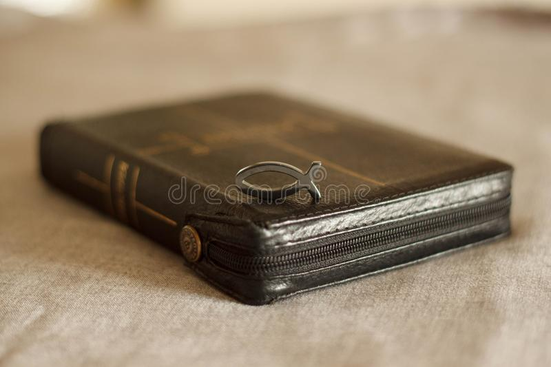 Picture of a book Bible close-up in black leather binding with a zipper with a Christian pendant symbol fish on a gray background.  stock photos
