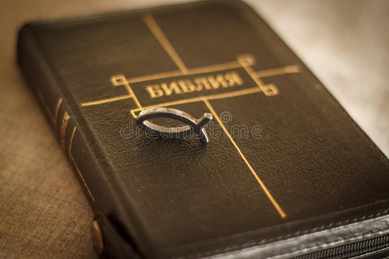 Picture of a book Bible close-up in black leather binding with a zipper with a Christian pendant symbol fish on a gray background.  stock images