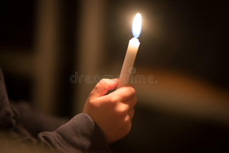 burning church candles in the hands of children on a dark background stock image