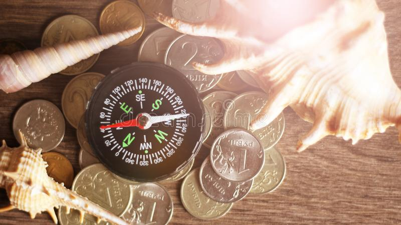 Picture of a Business Money Concept Idea Coins ,Compass and seashells royalty free stock photos