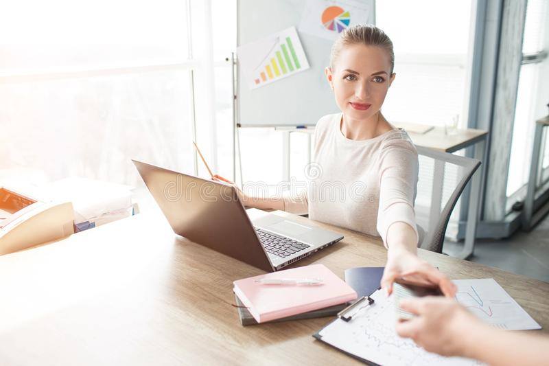 A picture of business woman getting her phone from her helper. She is preparing for skype meeting. stock image