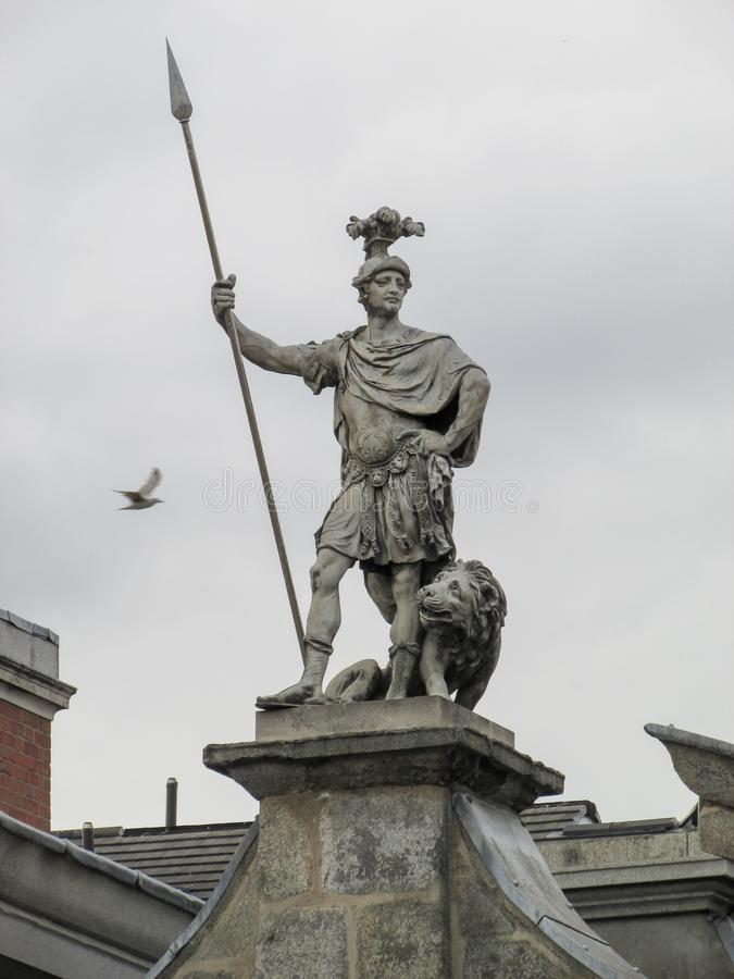 Statue Of Fortitude. Picture captured in Dublin`s Castle. Strong warrior and a lion as symbols of the strength of the nation. Holding a great spear while a bird stock photo