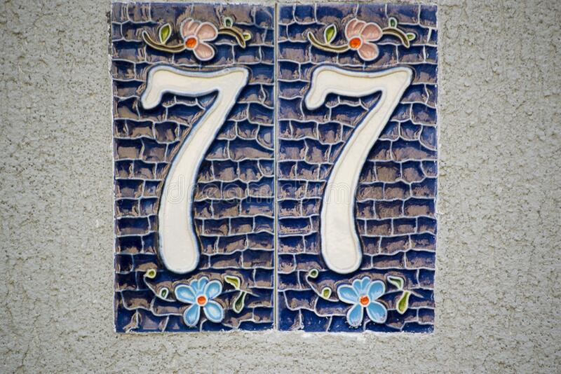 Picture of a ceramic house numbering plate with floral motifs. stock image