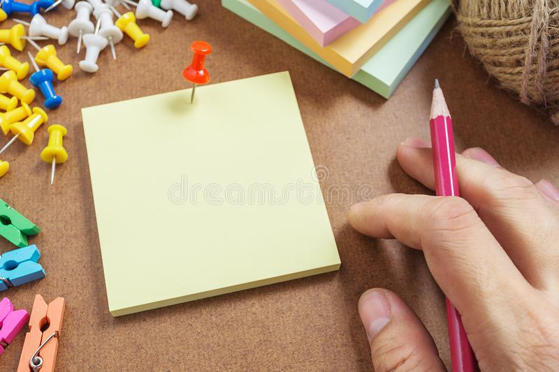 Picture close up note paper have red pin pinned. And hand prepare to write some text on it royalty free stock image