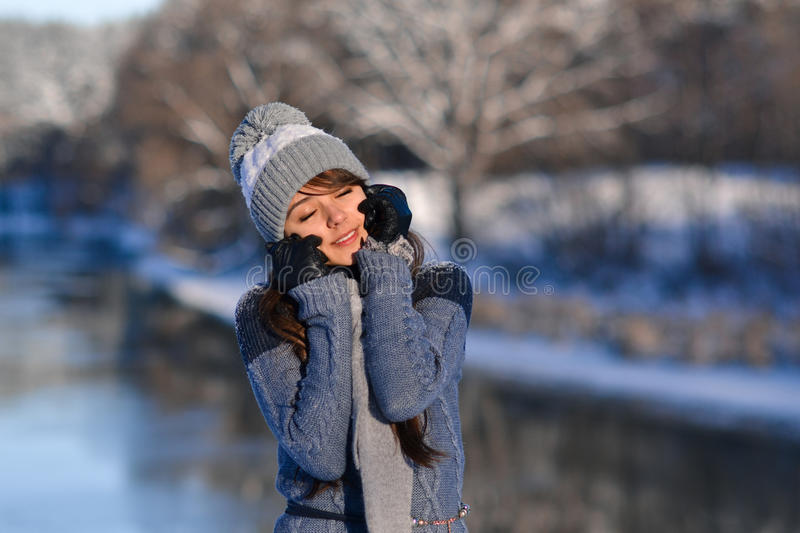 Picture of closed eyes sunny smiling beautiful cute girl enjoying a winter nature on winter snowy forest background. Portrait of b stock images