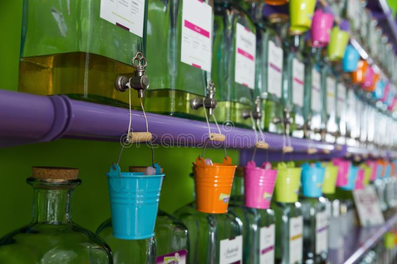 Picture of colored pails hanging on taps of perfume bottles. On shelves in store stock photography