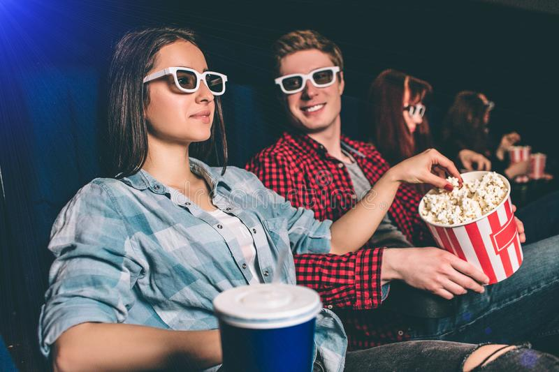 A picture of company sitting together in one row in cinema hall. Girl is watching movie in glasses and reaching the stock photo