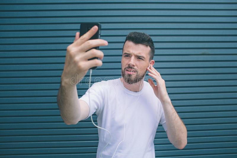 A picture of concentrated man looking at phone he has in hands. Guy is listening to music and posing. He is taking stock photo