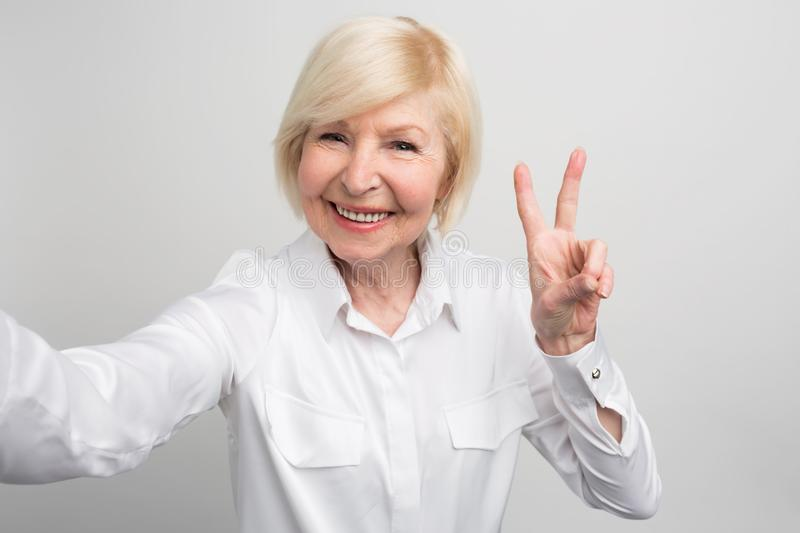 A picture of confident and modern granma that likes to take selfies. She knows everything about new trands in the world stock photography