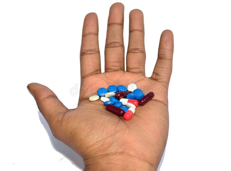 A hand holding colorful pills stock image
