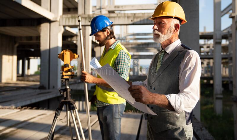 Picture of construction site engineer looking at blueprint stock photography