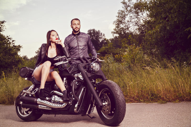 Picture with a couple of beautiful young bikers stock images
