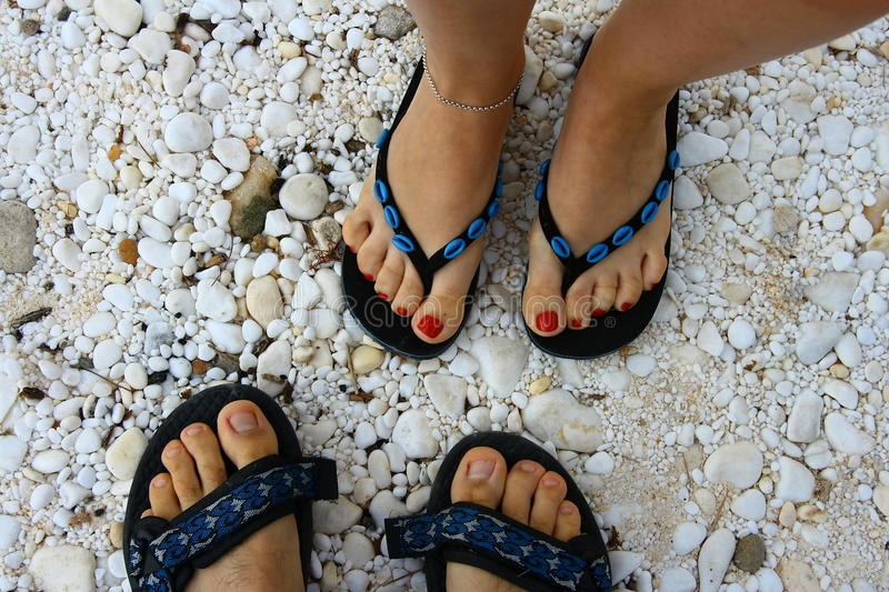 Picture of couples feet in slippers on beach royalty free stock image