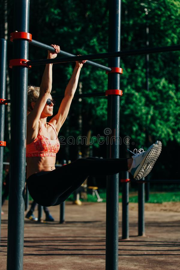 Picture curly blonde sports pulls up on sports simulator in park stock image