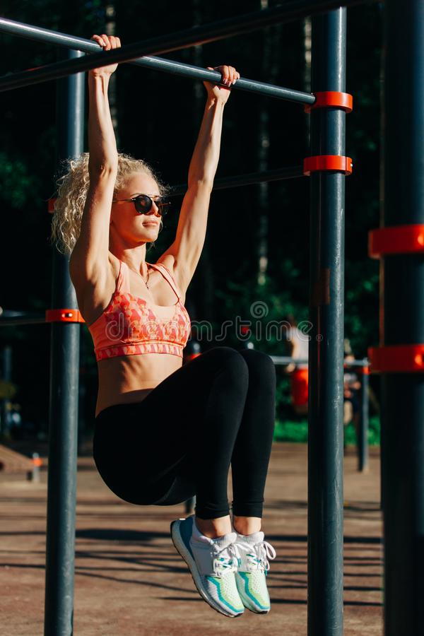 Picture curly blonde sports pulls up on sports simulator in park royalty free stock photo