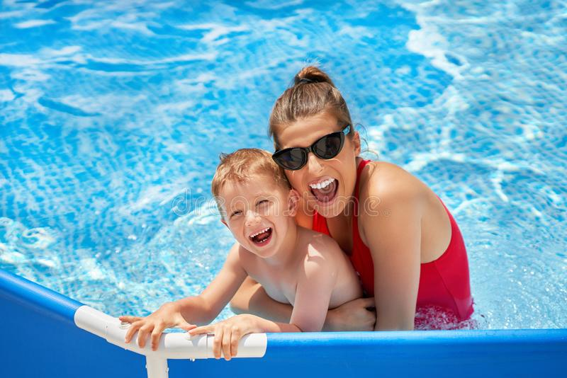 Cute boy with his mother playing in swimming pool during summer royalty free stock photo
