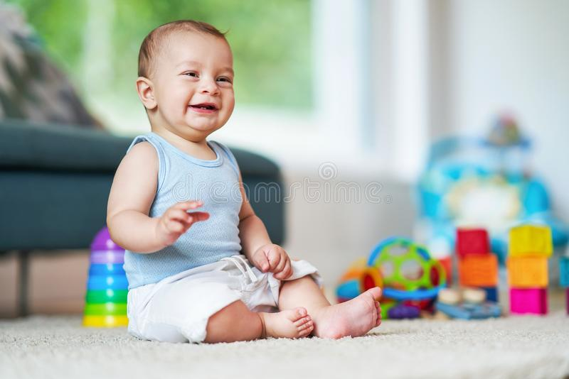 Cute smiling baby boy sitting on floor in living room stock photo