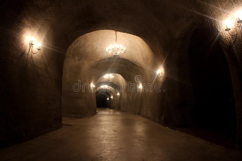 Dark tunnel with lights in a winery cellar royalty free stock photos