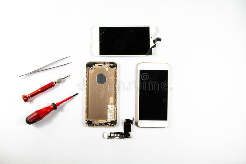 On the desk of a mobile repairman There is a damaged phone waiting to be repaired. royalty free stock image