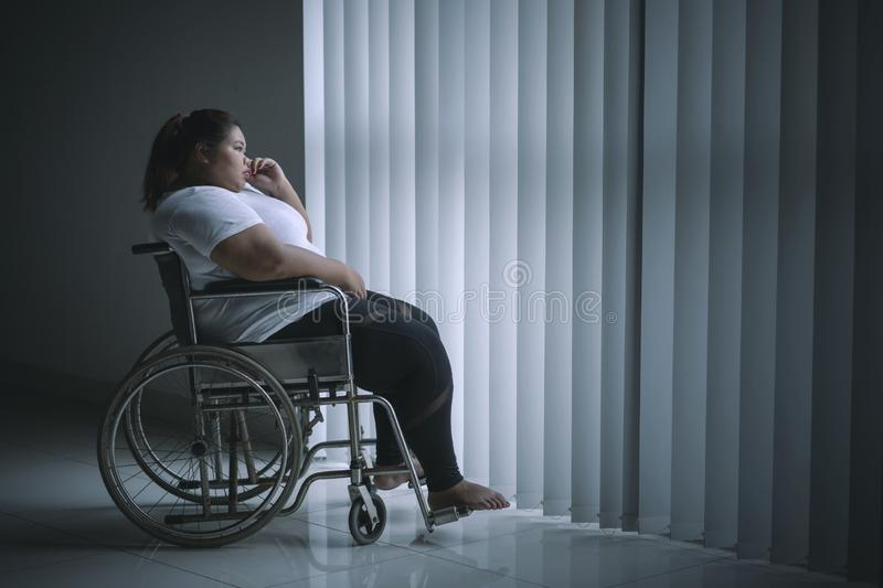 Disabled fat woman looks pensive near the window stock photo