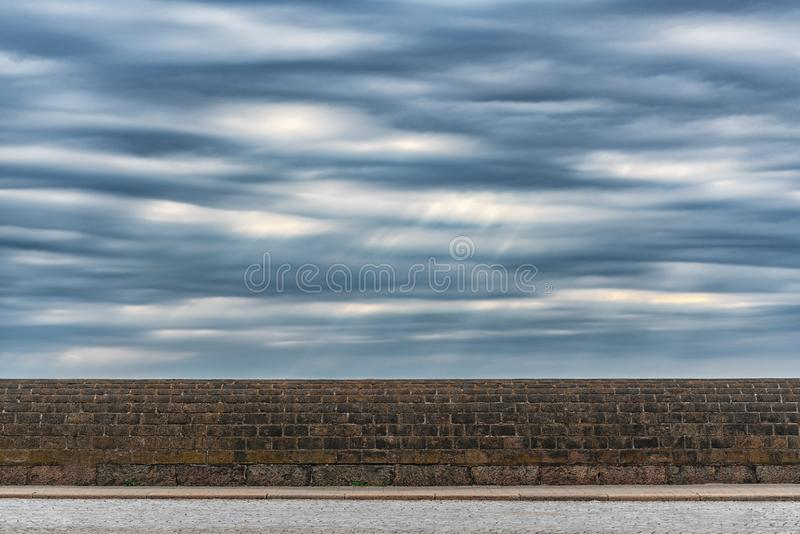 Picture of dramatic stormy sky with clouds over the stone wall royalty free stock image