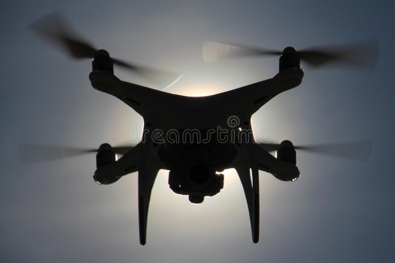Drone silhouette in the sky. Picture of a drone hovering in front of the sun against the blue sky background royalty free stock photos