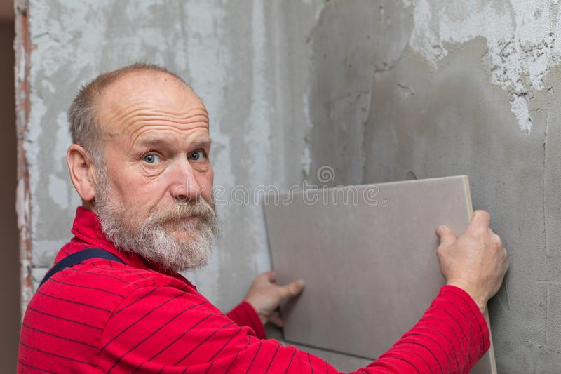 Elderly craftsman working with tiles stock photos