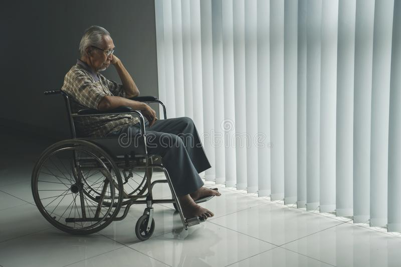 Disabled elderly man looks sad near the window. Picture of elderly man looks sad while sitting in the wheelchair near the window in the retirement home royalty free stock photography