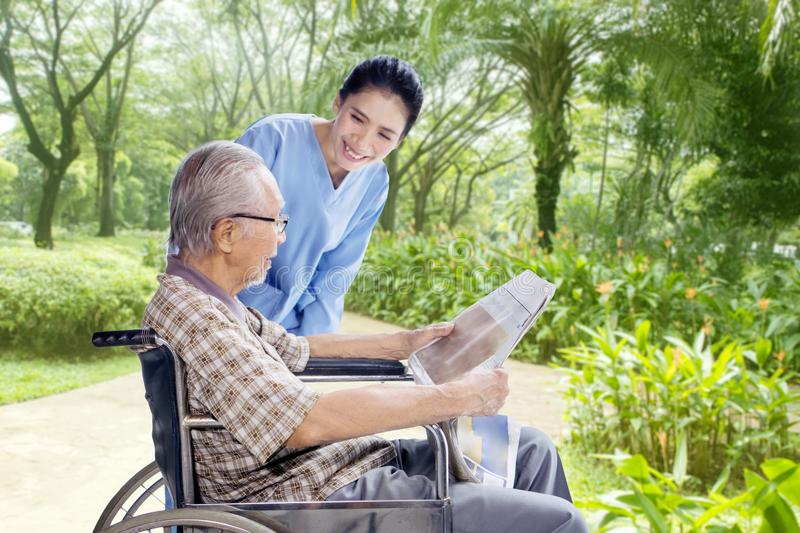Elderly man relaxing with his caregiver. Picture of an elderly men sitting on the wheelchair while relaxing with his caregiver in the park stock photography