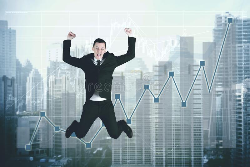 Successful businessman jumping with growth statistic stock images