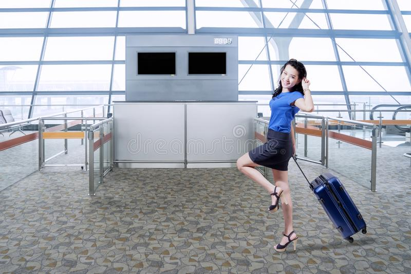Excited businesswoman walking in the airport royalty free stock image