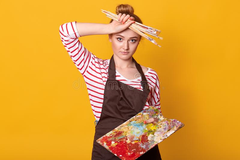 Picture of exhausted painter touching her forehead with hand, wiping out sweat, holding wide set of paintbrushes and dirty palette royalty free stock photography