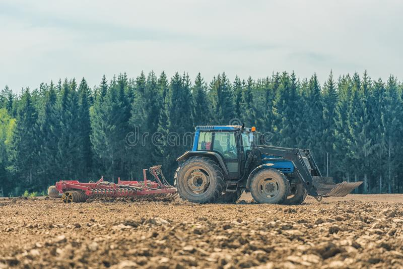 Picture of farmer plowing stubble field royalty free stock image