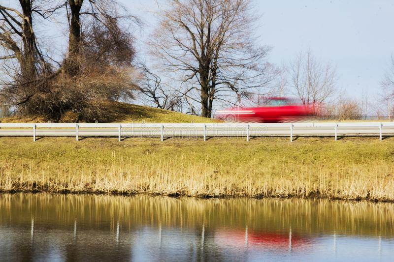 Fast red car going past a pond stock photography