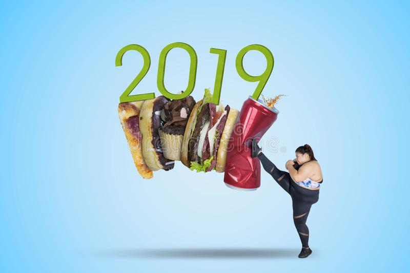 Fat woman kicks fast food and number 2019. Picture of fat woman kicking soft drink and fast food with number 2019 stock image