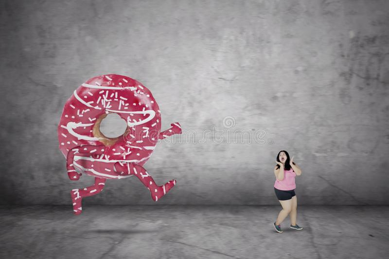 Sweet donut chasing fat woman stock image