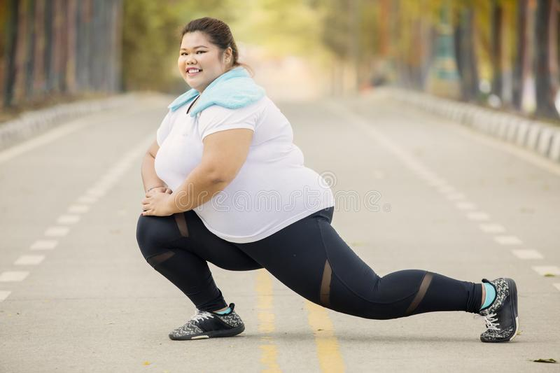Happy fat woman stretching legs on the road royalty free stock image