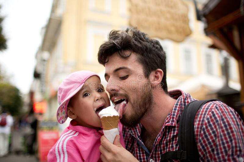 Picture of father liking white ice cream with daughter. Walking on sreet and have fun together. Tasty sweet ice cream. Spend time together stock photography