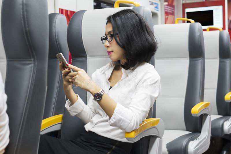 Female entrepreneur using a phone in train royalty free stock photography