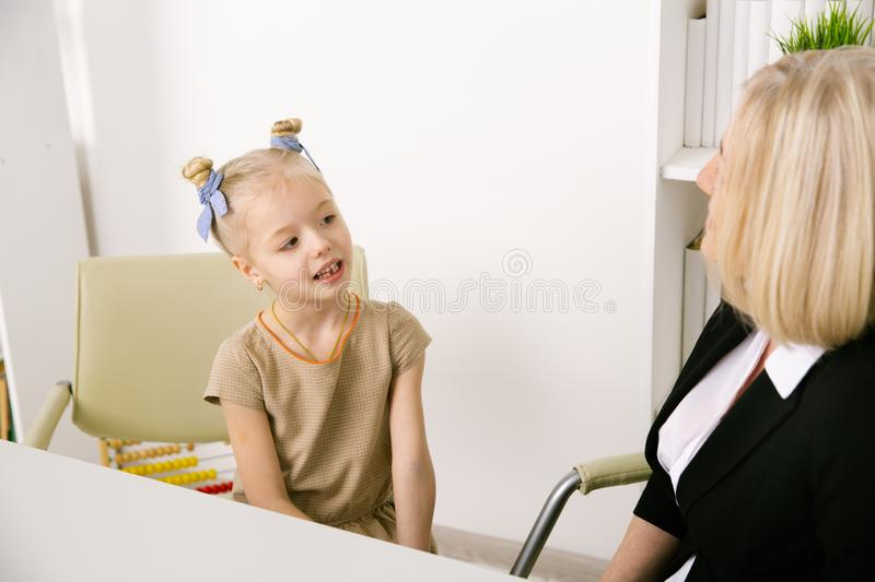Picture of female tutor helping little girl. Teacher and pupil concept. stock photography